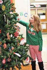 Third grader Brynlee Cardwell hangs her handcrafted Santa ornament on the Gap Creek Elementary School Christmas tree.