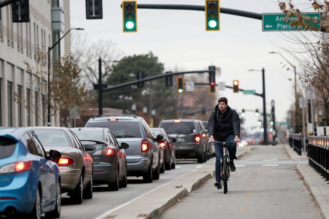 A cyclist rides along the bike lane on State Street, Tuesday, Nov. 26, 2019 in West Lafayette.