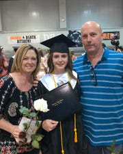 Katie with her parents, Jill and Leon Romero celebrating her graduation.