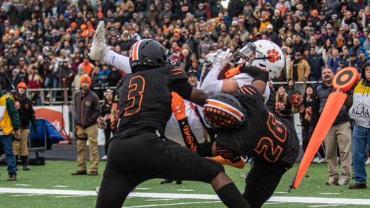 Nick Nemecek clutches the game-winning touchdown pass between Belleville defenders Jalen Williams (3) and Deshaun Lee (26) in a state Division 1 semifinal on Saturday, Nov. 23, 2019 at Howell.