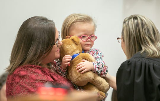 Ericka Poag holds her just-adopted daughter Eliana, 1, as Judge Miriam Cavanaugh speaks to Eliana. Eliana holds a Teddy bear presented to her by court referee Chelsea Thomason.