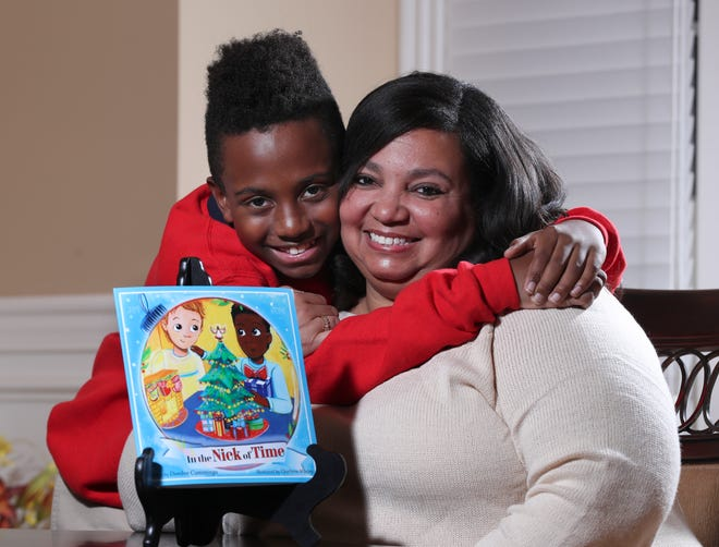 """Deedee Cummings, right, with her son Nick Cummings, 11, at their home in Louisville. Cummings was concerned that there are not many holiday books featuring people of color so she wrote a holiday book inspired by him called """"In the Nick of Time."""""""