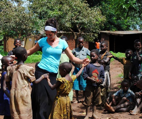 Amber Haubert, the owner of Global Coffee Co. with residents in Malawi, Africa during a four-month mission trip in 2013.