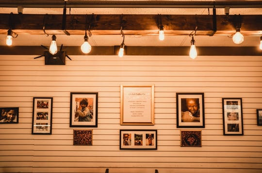 A wall inside Global Coffee Co. displays photos of people owner Amber Haubert met while serving on missions in Africa. Her coffee shop aims to make a difference, Haubert said.