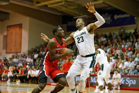 Georgia forward Mike Peake (30) tries to get to the basket over Michigan State forward Xavier Tillman (23) during the first half of an NCAA college basketball game Tuesday, Nov. 26, 2019, in Lahaina, Hawaii. (AP Photo/Marco Garcia)
