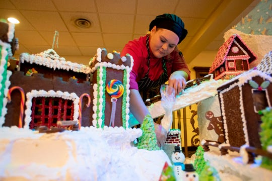 Pastry cook Angelica Perry puts frosting on the gingerbread village Tuesday, Nov. 26, 2019, at the Peabody Hotel in downtown Memphis.
