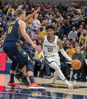 Memphis Grizzlies guard Ja Morant (12) dribbles the ball while Indiana Pacers forward Domantas Sabonis (11) defends in the second half at Bankers Life Fieldhouse in Indianapolis on Nov 25, 2019.