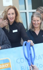 Board president for the YMCA of South Collier, Ashley Lupo, hands back the traditional outsize pair of scissors after the ribbon cutting. Next to her is events chair Fritzi Holmes.