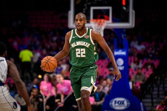 Khris Middleton brings the ball up court in a 2019 preseason game against the Mavericks.