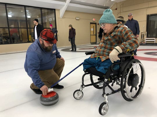 Ed Leblanc, a Vietnam War veteran, pushes off a curling stone with the help of a volunteer.