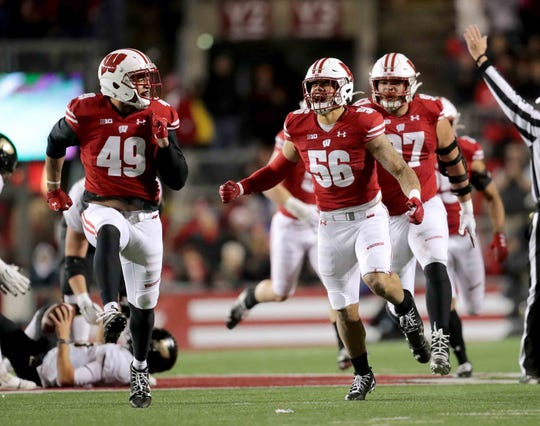 Chrisitan Bell (49) is chased by Zack Baun (56) and other Wisconsin teammates after the reserve linebacker recorded a key sack against Purdue on Saturday.
