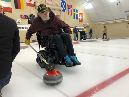Pete Mittelstaedt looks down the center of the ice before he throws his curling stone.