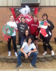 """The Flippin High School Art Club will be offering seasonal window painting to local businesses and friends on Tuesday. Pictured above are are FHS Art Club members (left to right) Sadie Akers, Rollins Jenkins, Caleb Warren, Kourtney Pence, (seated, middle) Payne Mousa and (front) Dominic Sellers.  These students are just a few of the students who will be """"painting the town"""" with holiday cheer. To schedule an appointment, please contact FHS art instructor Cheryl Blasdel by email at cherylblasdel@flippinschools.net or call (870) 453-2233."""