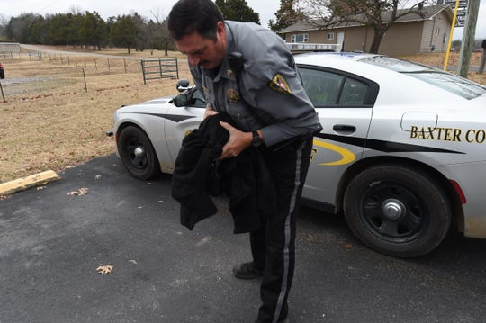 Sgt. Ken Grayham of the Baxter County Sheriff's Office brings an injured owl to All Creatures Animal Hospital Tuesday after the bird was struck by a car.