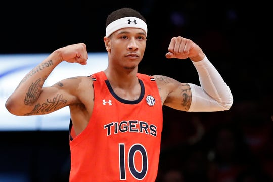 Auburn guard Samir Doughty (10) shows his muscles after scoring during the first half of an NCAA college basketball game against New Mexico in the Legends Classic, Monday, Nov. 25, 2019, in New York. Doughty was the high scorer for Auburn with 19 points as they defeated New Mexico 84-59. (AP Photo/Kathy Willens)