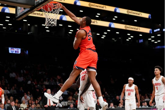 Auburn center Austin Wiley (50) dunks as New Mexico guards Makuach Maluach (10), JJ Caldwell (11) and Tavian Percy (4) watch from the floor during the Legends Classic in Brooklyn on Nov. 25, 2019.