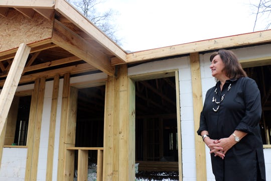 Judy Felts stands outside the Oak Cottage for Women, which is under construction on West Fowlkes Street on Nov. 26, 2019.
