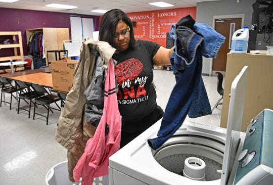 Community Activities coordinator Angelica Brooks-James washes clothes in the community room at Jere Baxter Tuesday, Nov. 26, 2019, in Nashville, Tenn. The school could use more help in getting supplies and volunteers to help parents.