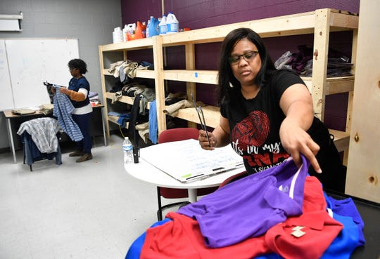Community Activities coordinator Angelica Brooks-James and Tempe Childs fold clothes in the community room at Jere Baxter Tuesday, Nov. 26, 2019, in Nashville, Tenn. . The school could use more help in getting supplies and volunteers to help parents.