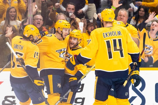 Predators center Nick Bonino (13) and his teammates celebrate his goal against the Blues in the first period Monday.