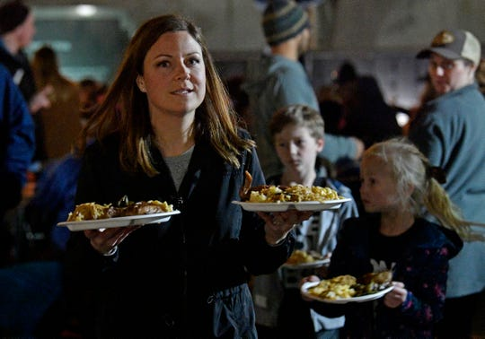 Elizabeth Claybaker delivers hot meals to residents as the Monday night program (People Loving Nashville) provides free meals for the homeless. Monday, Nov. 25, 2019, in Nashville, Tenn.