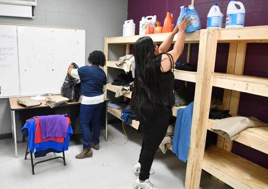 Community Activities coordinator Angelica Brooks-James washes, folds and organizes the laundry room at Jere Baxter with help from Tempe Childs, left, Tuesday, Nov. 26, 2019, in Nashville, Tenn. The school could use more help in getting supplies and volunteers to help parents.