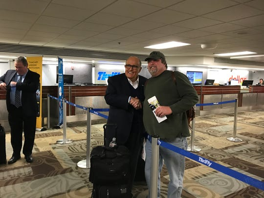 Rudy Giuliani poses for a photo with a traveler at Nashville International Airport Nov. 25, 2019.