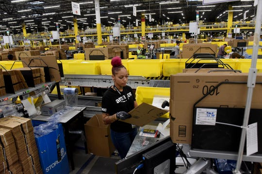 Amazon Distribution Center packer Shanayah Argus takes items from bins and prepares them for shipping on Tuesday, Nov. 26, 2019 at the company's Etna Township location.