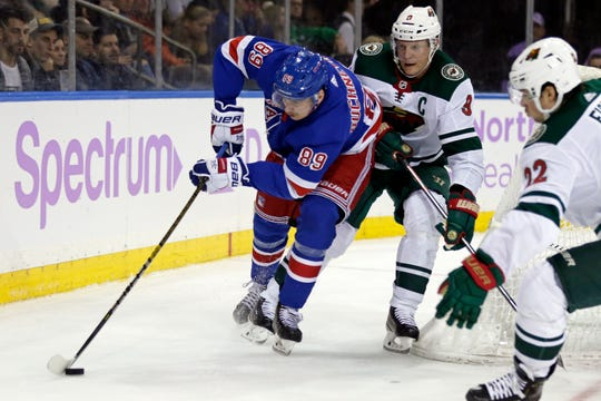 New York Rangers left wing Pavel Buchnevich (89) controls the puck in front of Minnesota Wild center Mikko Koivu (9) during the second period at Madison Square Garden.