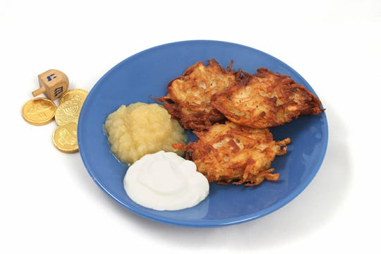 Potato pancakes (latkes) for Hanukah served with applesauce & and sour cream. Isolated with a dreidel & gelt.