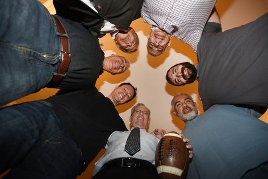 Group photo of the friends who have met every year since 1967 to play football on Thanksgiving (clockwise from the bottom center), Ron White (holding a ball), Ethan White, Scott Harris, Scott Reddin, Brad Chananie, Jonathan Chananie and Marco Rodriguez,  photographed in Englewood on 11/25/19.