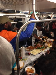 This Sunday, Nov. 24, 2019, photo provided by Wake Coulter shows a Thanksgiving meal being served on a New York City subway L Train.