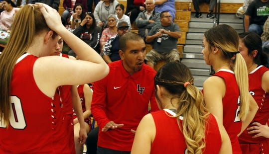 Loving head coach Derrick Martinez talks to his team during a timeout against the Carlsbad Cavegirls JV team on Nov. 25, 2019.