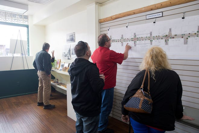 Community members and business owners look at a map of a redesigned West Main Street in downtown Farmington on April 5, 2018 at the Complete Streets headquarters.