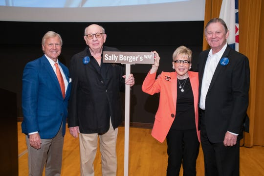 Michael Landes, Miles and Sally Berger and G. Aubrey Serfling show off Sally Berger's street sign.