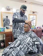 John Oliver talks Tuesday about challenges contributing to unemployment in the black community while cutting Deborah Phillips' hair at The Network barbershop in Pensacola.