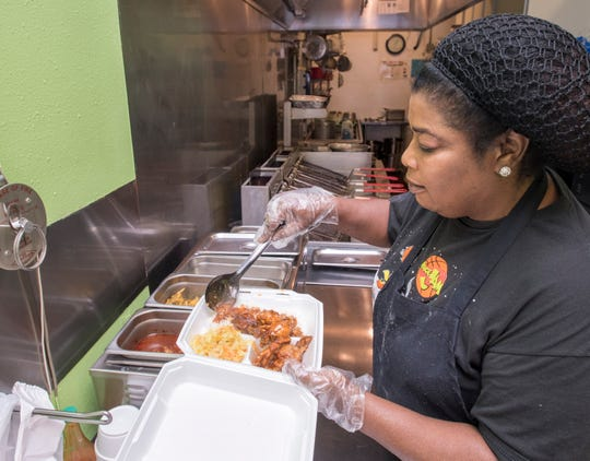 Carolyn Sutherland plates a Jamaican Special, which includes chicken wings, rice and vegetables, at Island Fish and Grits in Pensacola.