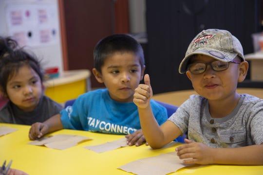 Aiden Gonzalez, left, Zyvier French, and Colten Huma, sample pumpkin seeds during a pre-kindergarten program at Salt River Elementary School.