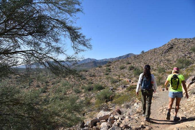 Hikers traverse a ridge on the Maricopa Trail/Mule Deer Trail in White Tank Mountain Regional Park.