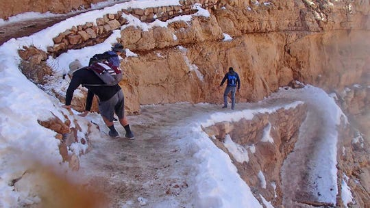 Two hikers make their way down an icy trail at Grand Canyon National Park.