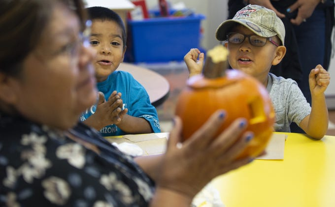 Zyvier French and Colten Huma, react after seeing a carved pumpkin during a pre-kindergarten program at Salt River Elementary School