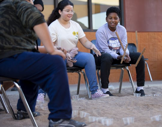 """Angel Little (left) and Jaheim Anderson, sixth graders at Salt River Elementary, play a Piipaash game """"Kinse"""" during school."""