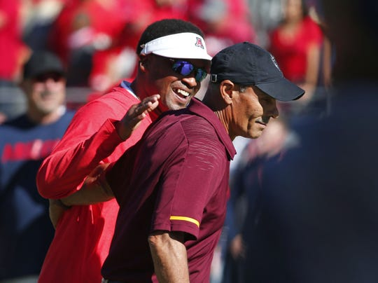 Arizona Wildcats head coach Kevin Sumlin shares a laugh with Arizona State Sun Devils head coach Herm Edwards before the Territorial Cup football game at Arizona Stadium in Tucson on November 24, 2018.