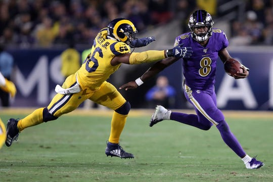 Lamar Jackson corre el ovoide ante el acoso del defensivo de Rams.