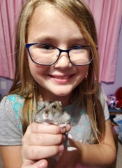 """Abby, with her pet hamster """"Tracy"""" that she was able to pick out herself as a gift last year for Christmas."""