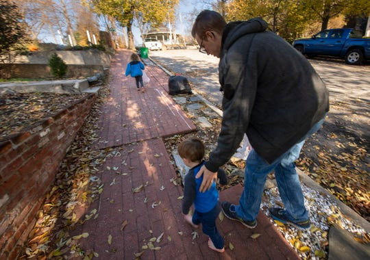 Tyler Snelbaker, right, gives his son encouragement as they walk up Lincoln Street in York during a trip around the block to pickup trash.