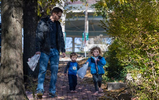 From the left, Tyler Snelbaker walks down Lincoln Street in York with his children Spencer, age 2, and Charlotte, age 3, as they pick up trash in their York neighborhood.