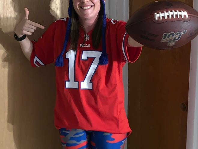 """Jennifer Drumm, 31, of Scottsville and her Josh Allen game ball. She turned down cash offers of $500 for the ball, and instead """"I'm getting a case for it,'' she said."""