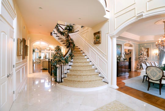 The front entrance shows a grand stairway along with the dining room on the right and the kitchen straight ahead.