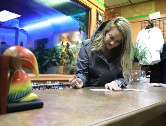 Rachel Eubanks, owner of Toucan Tans on Hilltop Drive, writes out a gift certificate on Tuesday, Nov. 26, 2019. Eubanks is a member of Women of Vision, the group that's organizing Redding's third annual Small-Business Saturday Scavenger Hunt. Participating stores will offer specials to celebrate the local shop-crawl.